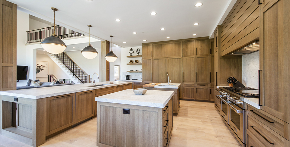 Large gourmet kitchen with marble countertops and light cabinets