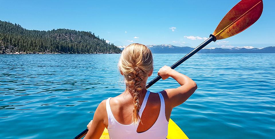Girl kayaking on Lake Tahoe in the Summer 2020 travel goals